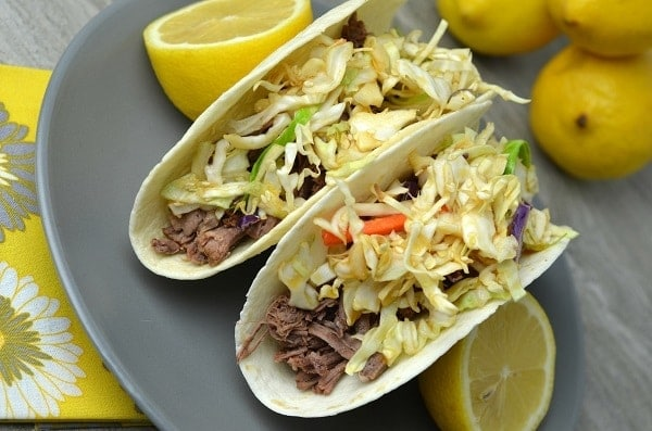 Asian Tacos next to lemon halves on a gray plate on a yellow flower cloth on a gray table