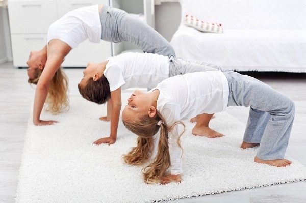 a mom and her kids doing stretching exercises on the floor of a bedroom
