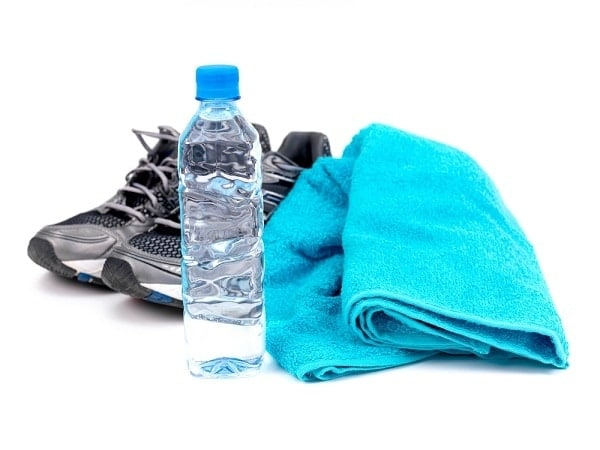 tennis shoes, a water bottle, and a blue towel on a white background