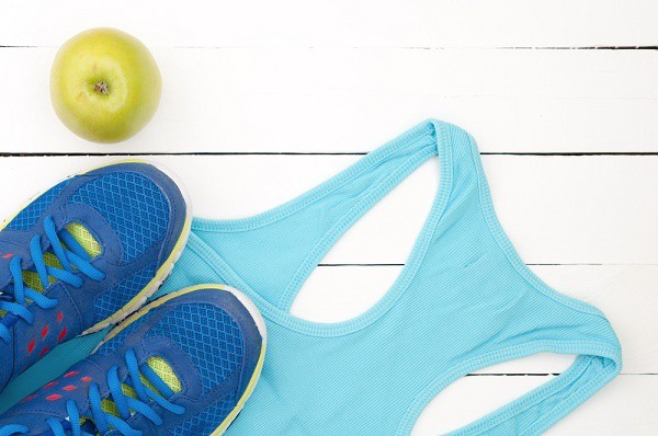 tennis shoes on a blue tank top next to a green apple on a white wooden table