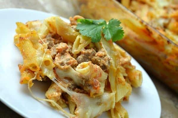 lasagna casserole on a white plate topped with parsley with a dish of lasagna casserole in the background