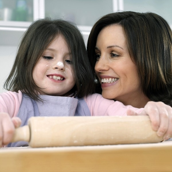 a mother watching her daughter use a rolling pin in a kitchen