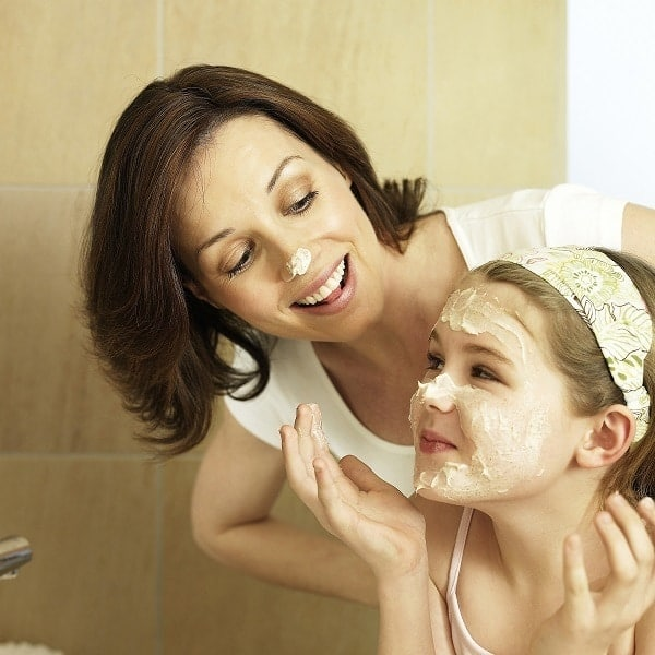 a mother and daughter putting on a home spa treatment