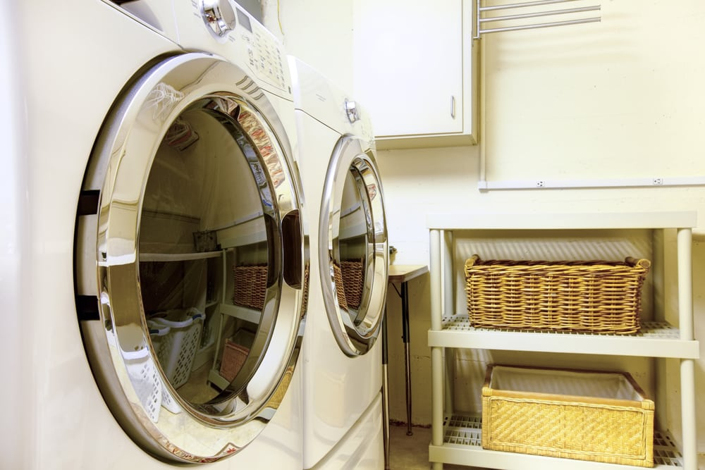 washer and dryer, cabinets, baskets in shelves, in a laundry room