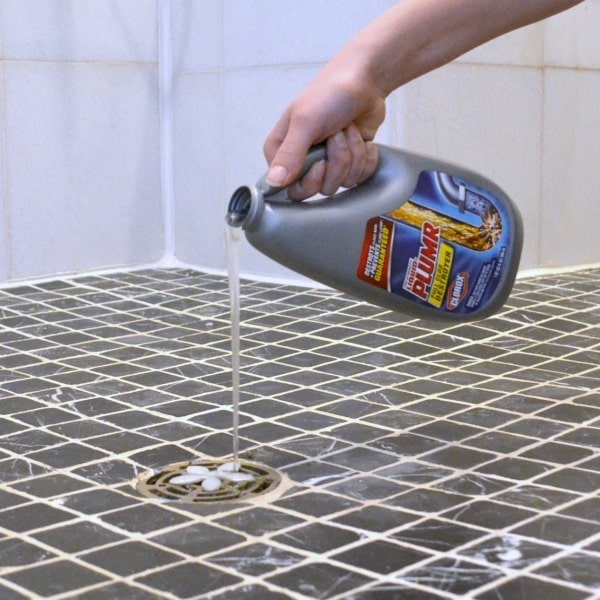 a hand pouring liquid plumr down a shower drain
