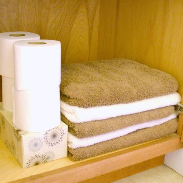 stacked tissue box, toilet paper, and white and brown towels in a bathroom cupboard