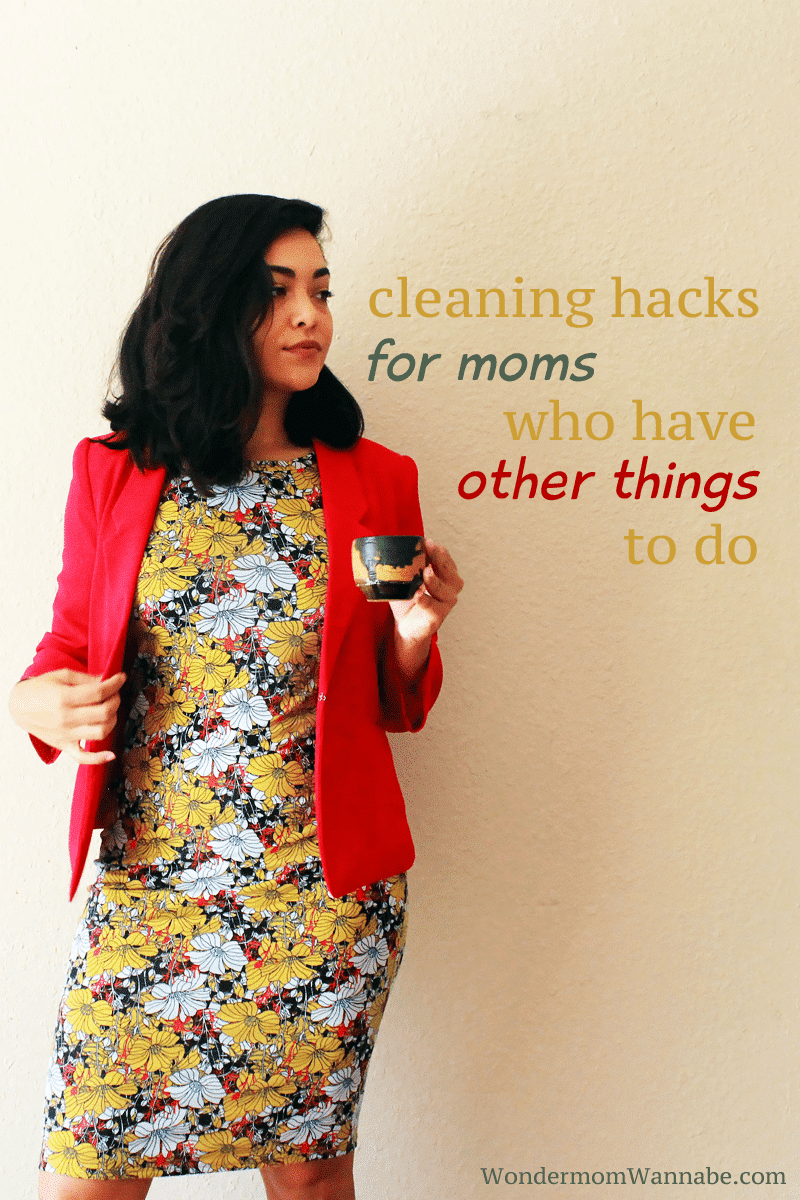 a lady holding a mug standing against a wall with title text reading Cleaning Hacks For Moms Who Have Other Things To Do