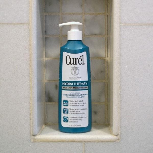 a bottle of Curel hydratherapy wet skin moisturizer in a shelf in a shower