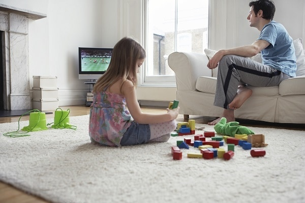 a girl sitting on the family room floor playing with toys while the dad sits on the couch watching tv
