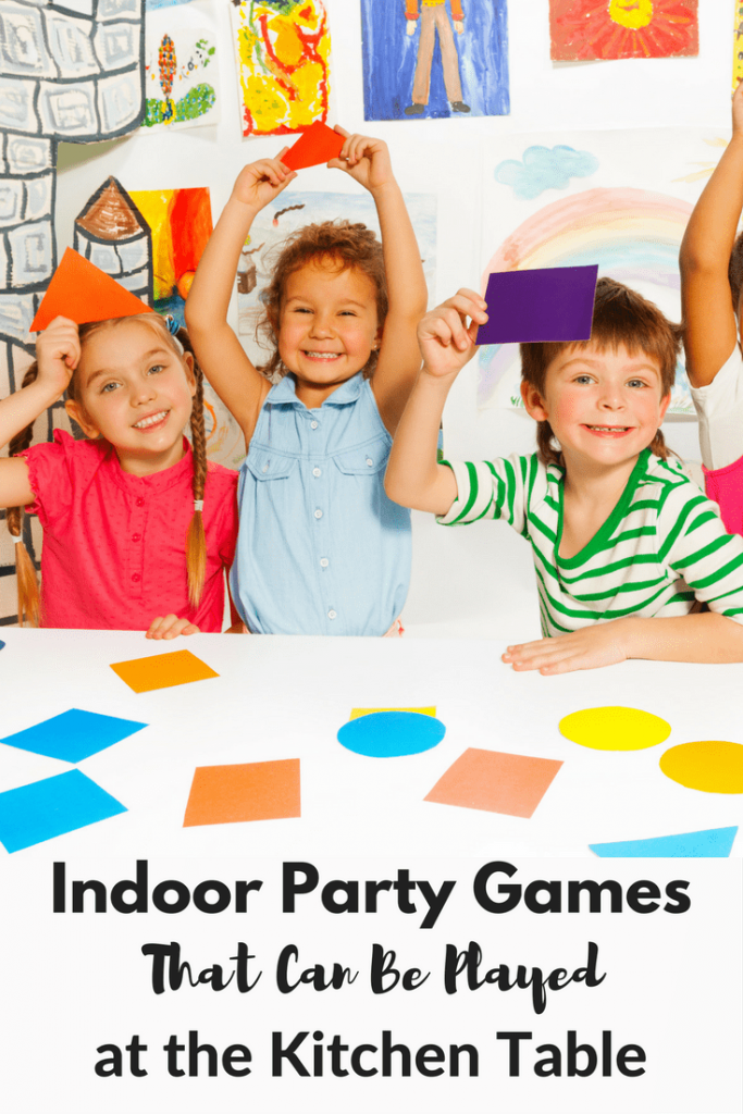 kids holding up colored shapes in front of a white table with more colored shapes on it with artwork on a wall in the background with title text reading Indoor Party Games That Can Be Played at the Kitchen Table
