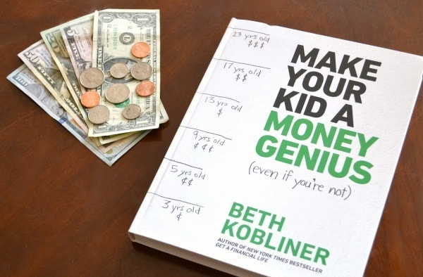 dollar bills and coins next to the Make Your Kid a Money Genius (Even if You're Not) book on a brown table