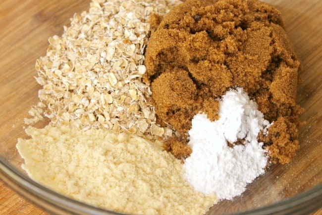 dry ingredients for No Flour Peanut Butter Protein Cookies in a glass mixing bowl on a brown table