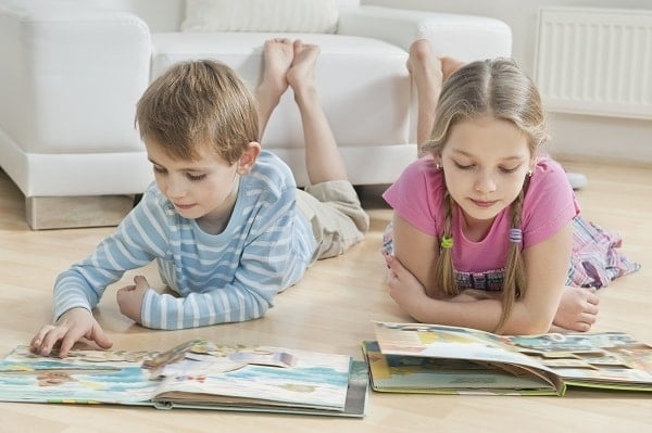 a boy and girl reading books while laying on a wood floor in a family room