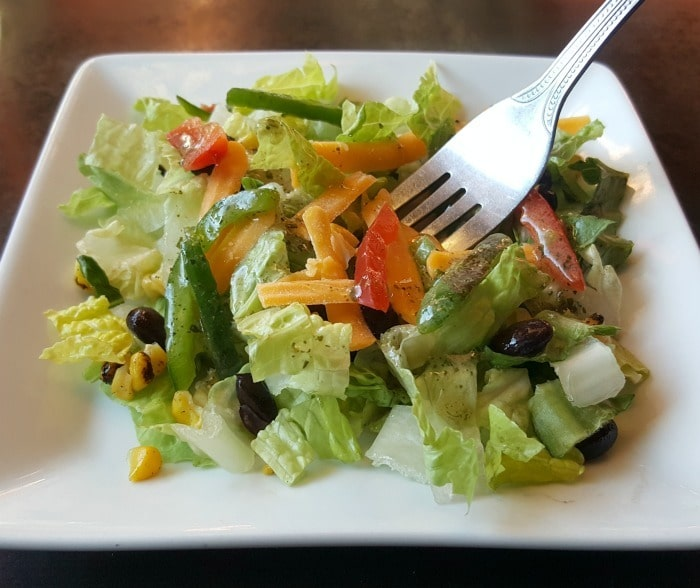 a fork in a salad on a white plate on a brown table as an example of How to Enjoy a Healthy Family Dinner Out