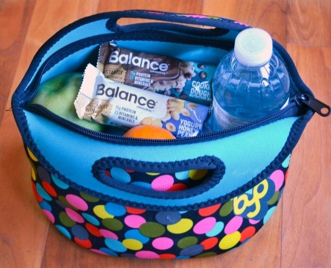 a bag with snacks and water in it on a brown background