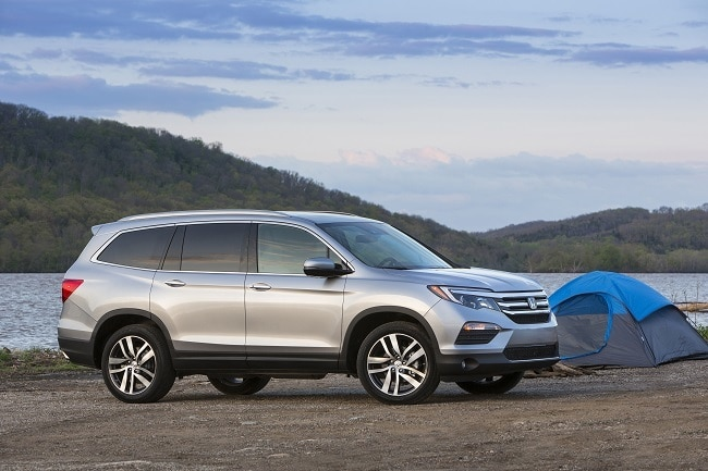 2017 Honda Pilot next to a tent with mountains in the background