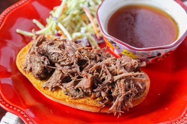 french dip sandwich on a red plate next to coleslaw and a bowl of sauce