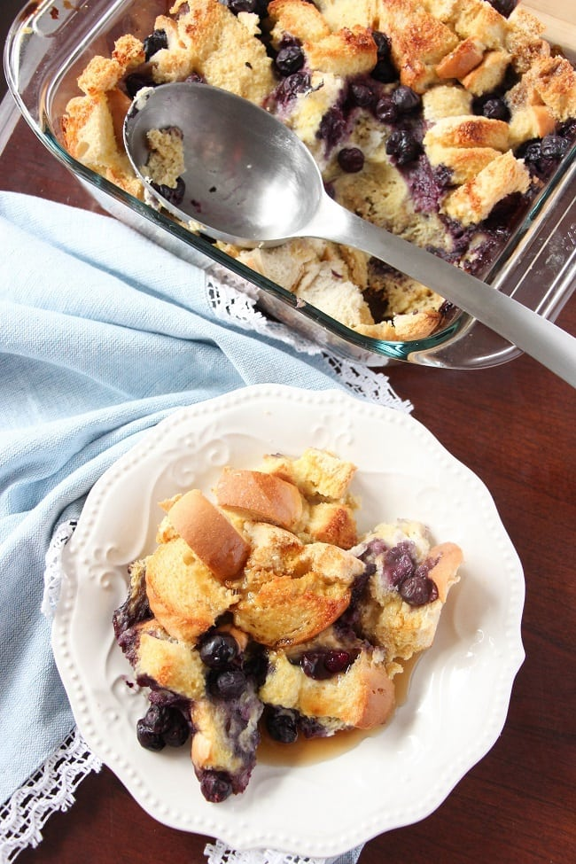 some blueberry french toast casserole on a white plate on a brown table next to a blue linen next to a glass baking dish of the rest of the casserole with a metal spoon in it