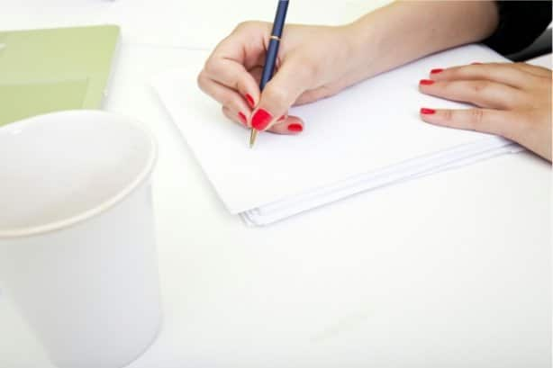 a lady writing in a notebook next to a phone and a white cup