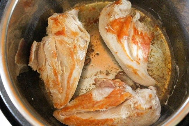 chicken breasts being browned in an instant pot