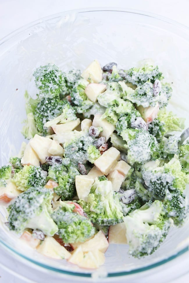 broccoli salad coated with dressing in a glass bowl on a white table