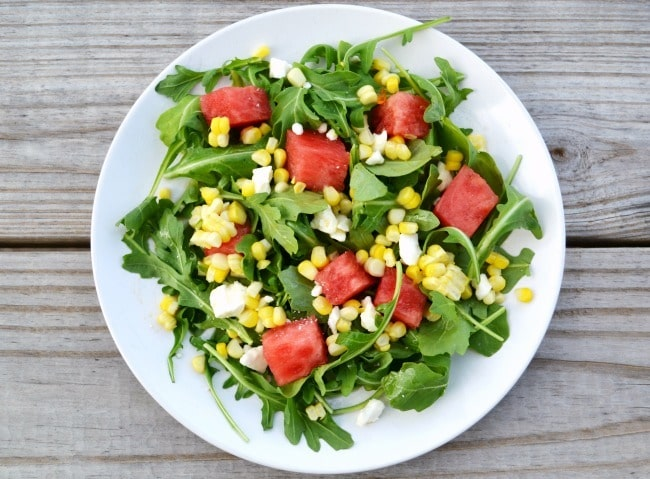 corn and watermelon salad on a white plate on a brown table