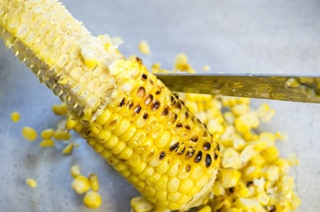 a knife being used to remove the kernels from a grilled corn on the cob