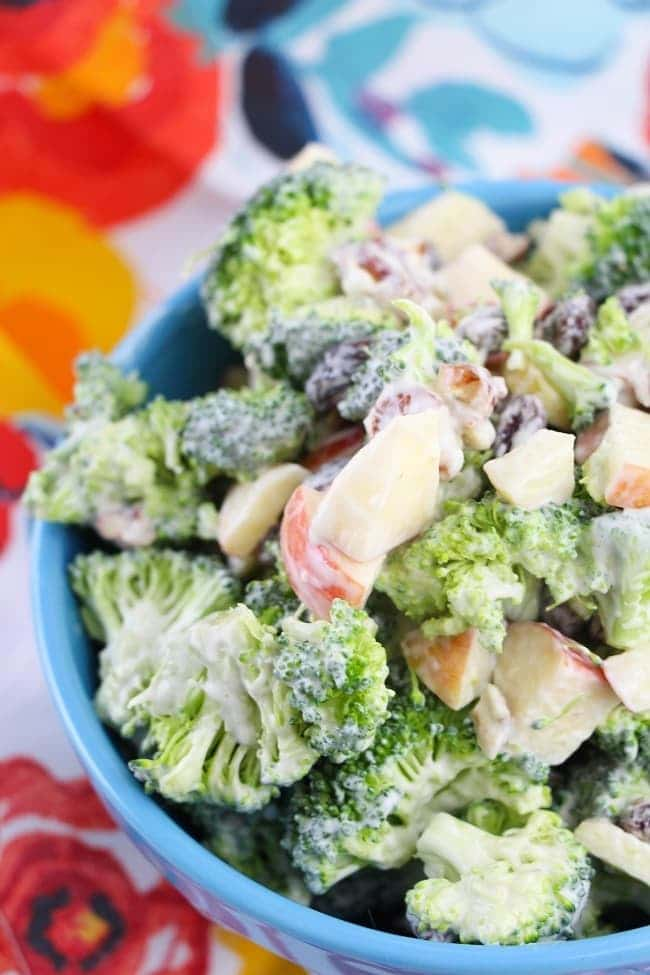 broccoli salad in a blue bowl on a floral linen