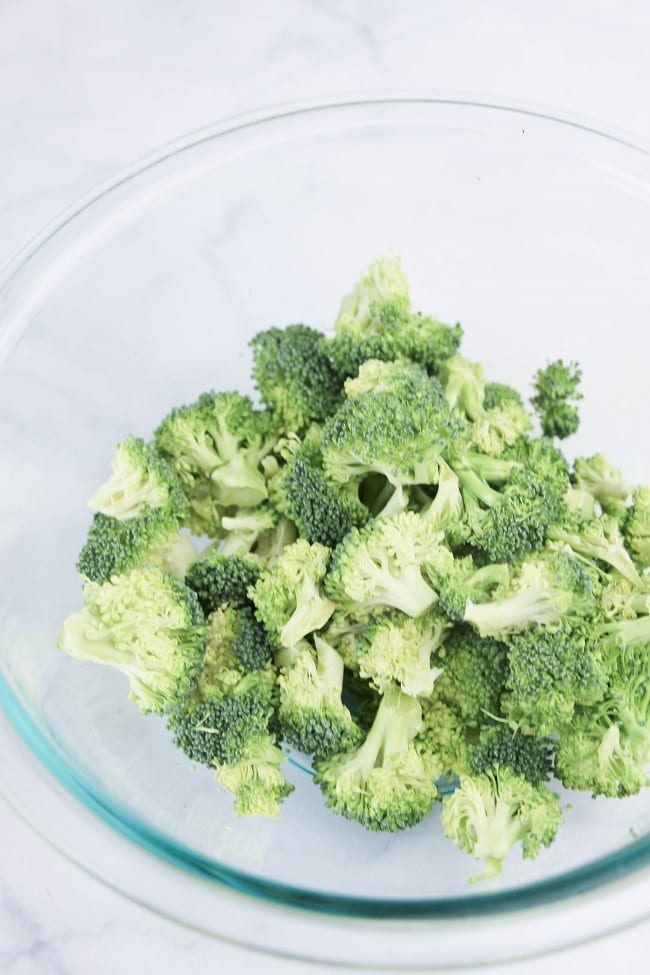 a glass bowl of chopped broccoli on a white table