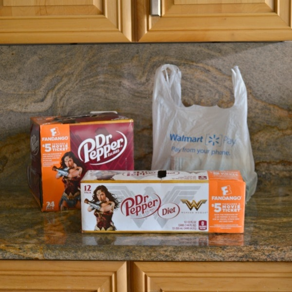 two packs of Dr. Pepper in Wonder Woman packaging on a kitchen counter next to a walmart plastic bag