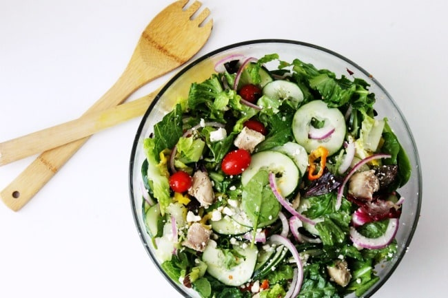 overhead view of Greek salad in a glass bowl next to a wooden spoon and fork on a white background