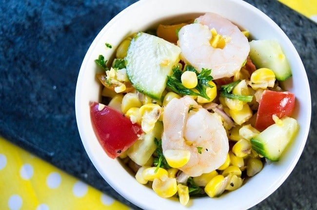 grilled corn salad topped with shrimp in a white bowl on a blue and yellow cloth