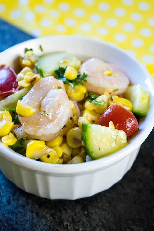 grilled corn salad in a white bowl on a blue cloth on a yellow and white polka dot paper