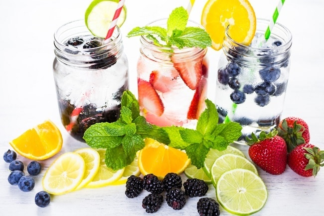 infused water in three glass mason jars with various fruit around them on a white background