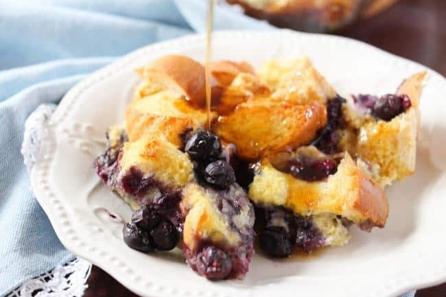 french toast casserole on a white plate next to a blue cloth