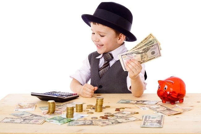 a boy holding money looking at a calculator on a table with more money on it and a red piggy bank
