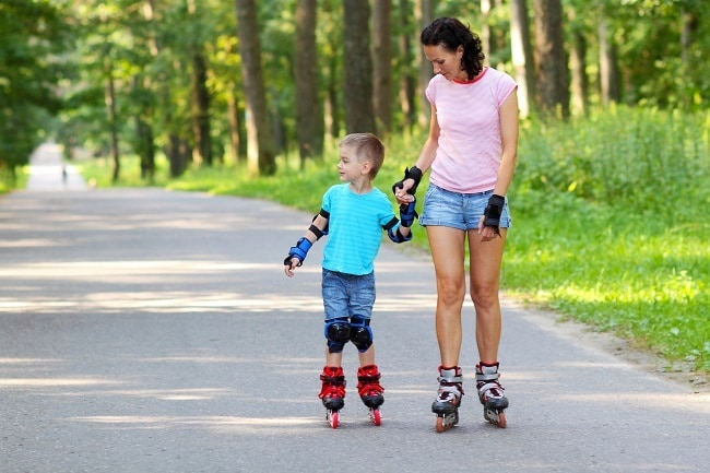 a mother and son roller blading on a path outdoors