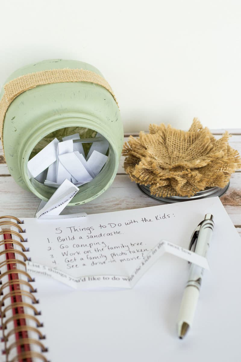 a journal notebook with a pen on it next to a green jar filled with strips of paper