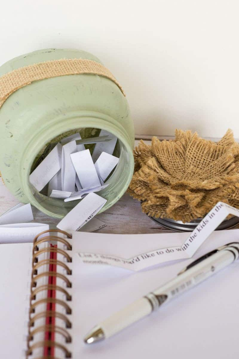 a notebook, pen, burlap flower, green glass jar filled with strips of paper