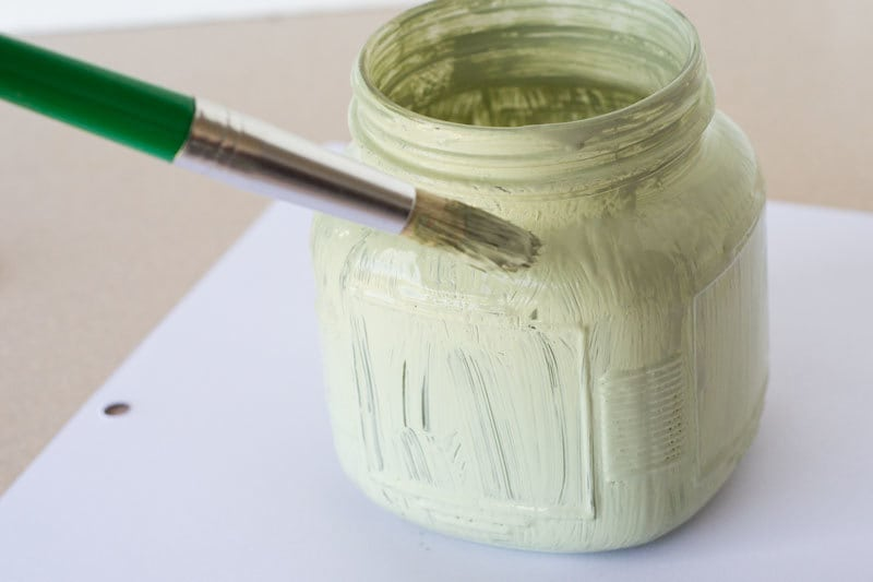 a paint brush applying green paint to a glass jar