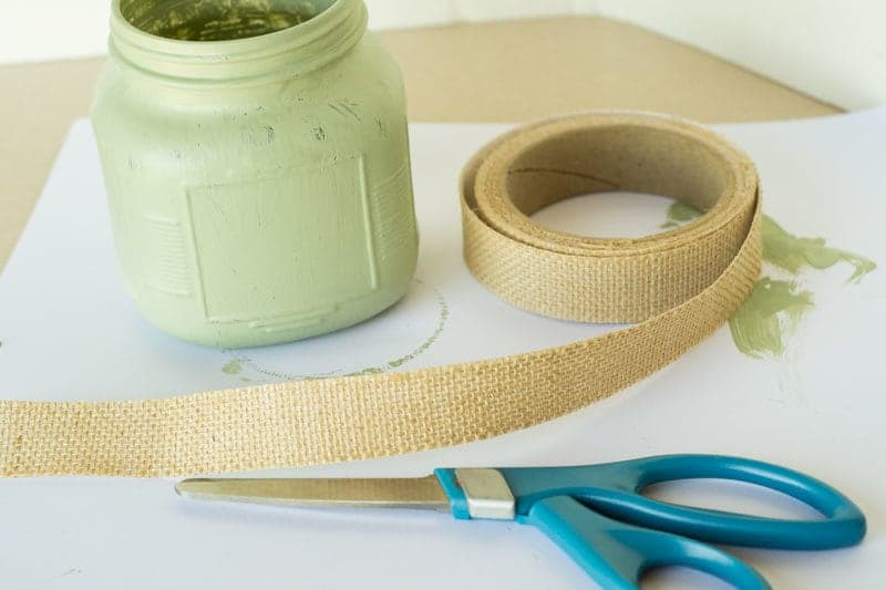 a green painted glass jar with burlap tape and scissors on a white piece of paper