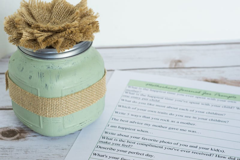 a piece of paper with journal prompts on it, next to a green glass jar wrapped with burlap tape with a burlap flower on the lid