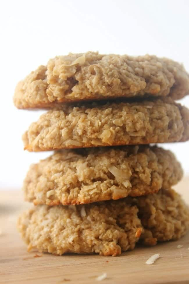 a stack of four coconut oatmeal protein cookies on a wood table on a white background