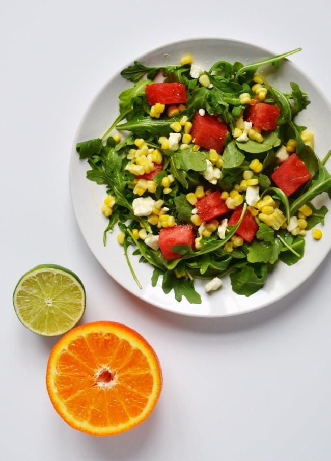 corn and watermelon salad on a white plate on a brown table with a slice of orange and lime next to it