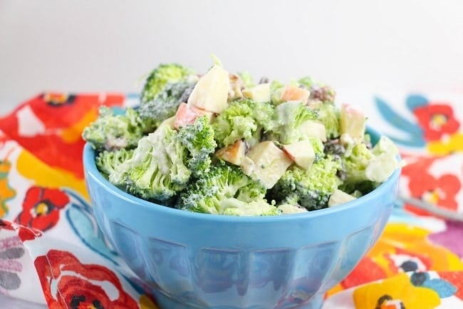 creamy broccoli salad in a blue bowl on a flower cloth