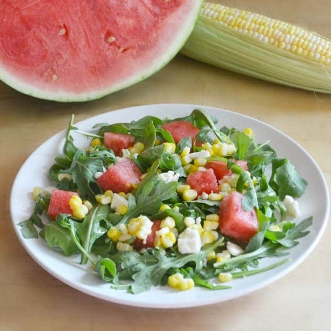 corn and watermelon salad on a white plate on a table with watermelon and corn on the cob in the background