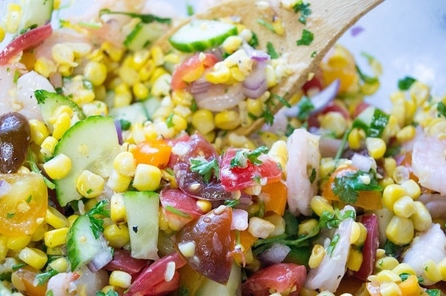 a wooden spoon being used to stir together the ingredients for grilled corn salad with shrimp