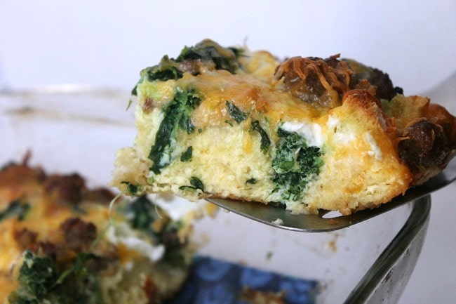sausage and spinach strata on a spatula above a glass dish of more food