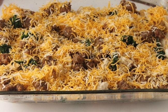 cubed stale french bread, sausage and spinach topped with shredded cheese in a glass baking dish