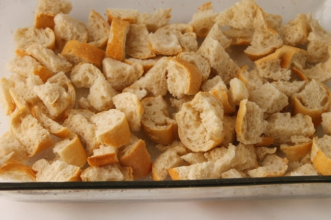 cubed stale french bread in a glass baking dish